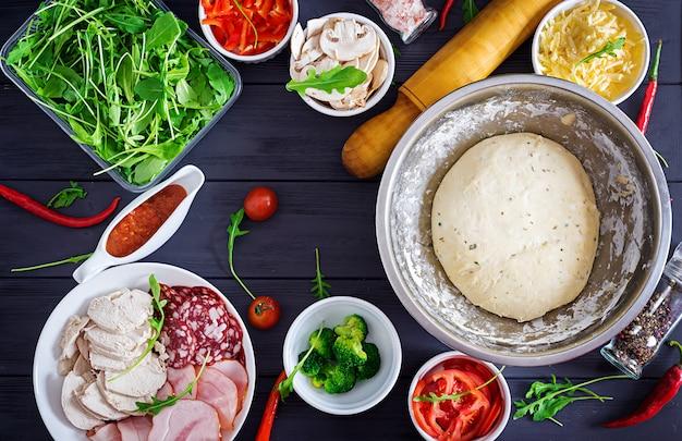 Pizza italienne. ingrédients de la pâte et de la pizza. pâte, fromage, tomates, brocoli, champignons, salami, jambon, filet de poulet ou boulangerie. vue de dessus