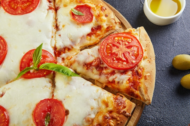 Pizza italienne et ingrédients pour cuisiner sur un fond de béton noir. tomates, olives, basilic et épices. triangle de pizza en tranches. copiez l'espace pour le texte. mise à plat