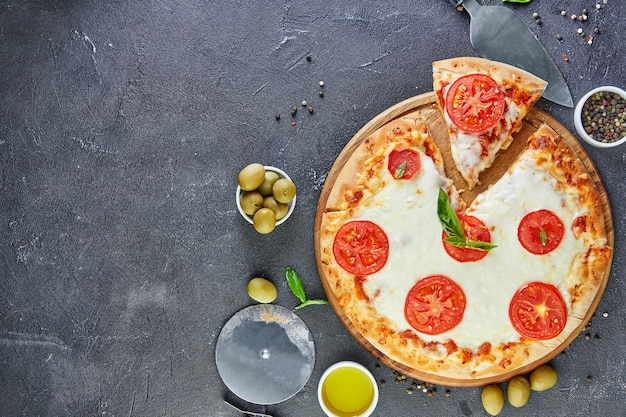 Pizza italienne et ingrédients pour cuisiner sur un fond de béton noir