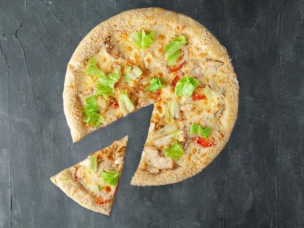 Pizza italienne. avec poitrine de poulet grillée, tomates, laitue, mozzarella et parmesan, vinaigrette césar. un morceau est coupé de la pizza. vue d'en-haut. sur un fond de béton gris. isolé.