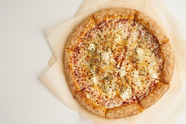 Pizza italienne à quatre fromages sur la vue de dessus de papier sulfurisé
