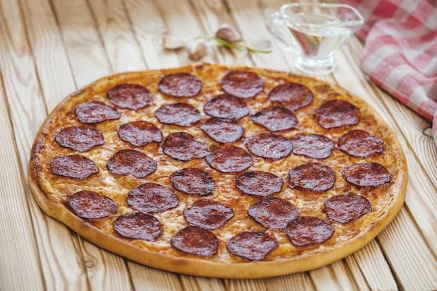Pizza italienne avec saucisse salami sur une table en bois savoureuse et appétissante