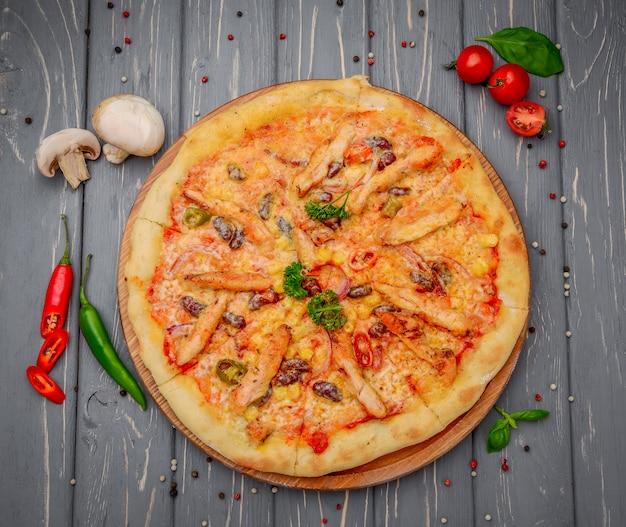 Pizza italienne traditionnelle avec poulet et haricots sur table en bois