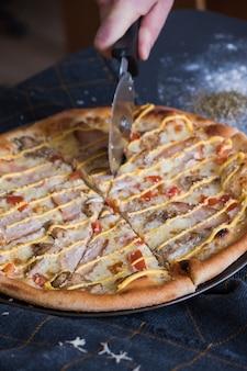 Pizza italienne traditionnelle avec des poulets sur une table en pierre bleue foncée. un homme coupe une pizza avec un couteau