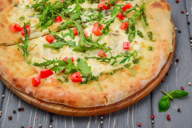 Pizza italienne traditionnelle avec roquette sur table en bois