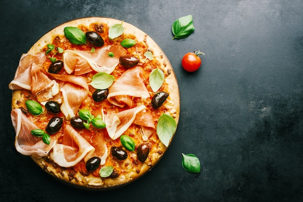 Pizza italienne traditionnelle sur table sombre