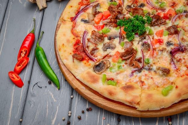Pizza italienne traditionnelle avec viande hachée sur table en bois