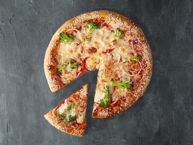 Pizza italienne végétarienne. avec brocoli, tomates, oignons, sauce tomate, mozzarella et sulguni. côté large. un morceau est coupé de la pizza. vue d'en-haut. sur un fond de béton gris. isolé.