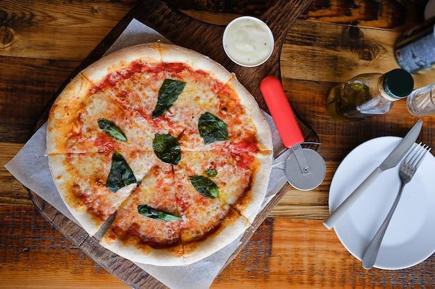 Pizza italienne végétarienne margarita avec fromage mozzarella, tomates, épices et basilic frais, sur une planche de bois.