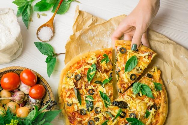 Pizza et main se bouchent sur blanc