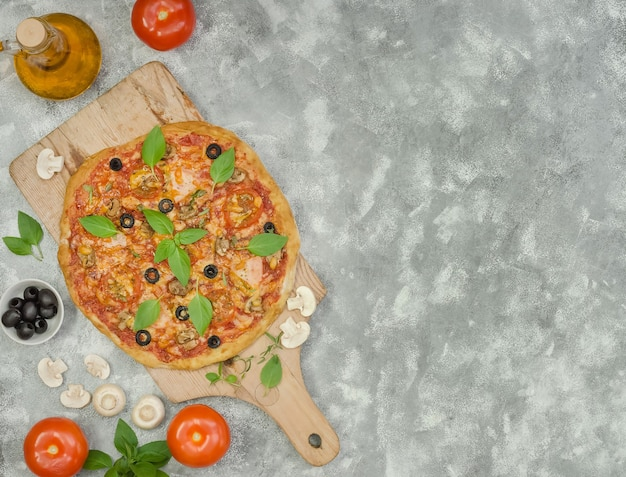 Pizza maison au jambon et ingrédients sur fond gris avec espace copie