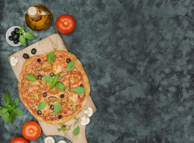 Pizza maison au jambon et ingrédients sur fond noir avec copie espace