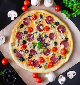 Pizza maison au salami, champignons et tomates cerises sur fond noir. vue de dessus.