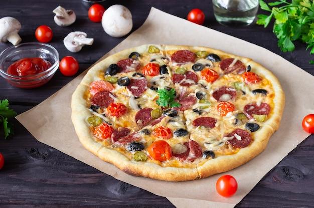 Pizza maison au salami, champignons et tomates cerises sur fond sombre. vue de côté.