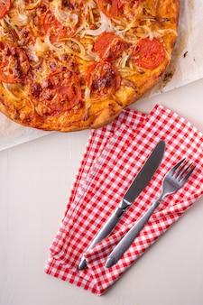Pizza maison chaude avec de la viande de poulet, des tomates, des oignons près de fourchette et couteau à couverts sur une nappe rouge, mise à plat, vue de dessus