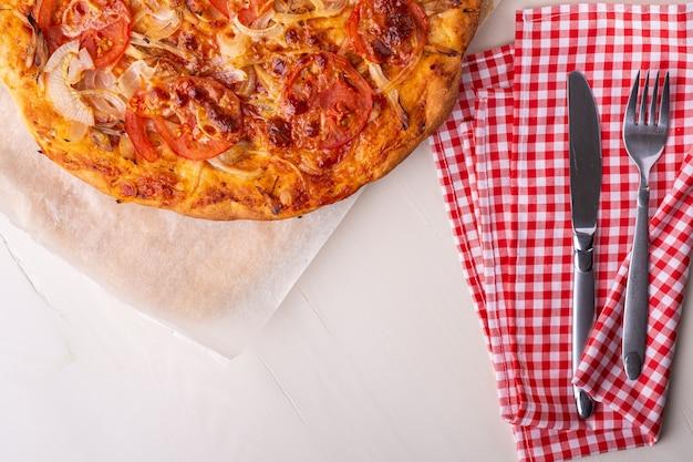 Pizza maison chaude avec viande de poulet, tomates, oignons près avec fourchette à couverts et couteau sur nappe rouge