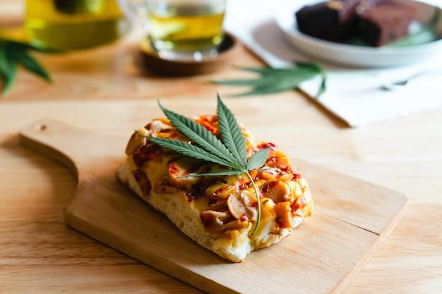 Pizza maison avec feuille de marijuana ou de cannabis sur plateau en bois.