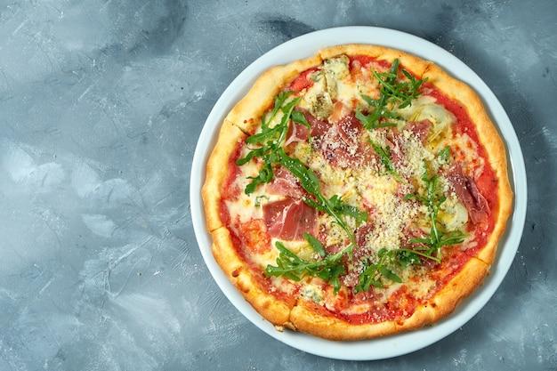 Pizza maison avec jambon, roquette et parmesan dans une assiette blanche sur béton, vue du dessus