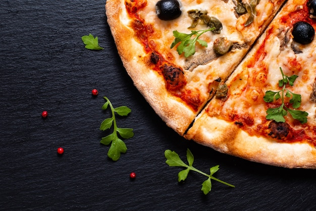 Pizza maison napoli ou anchois pizza sur pierre d'ardoise noire