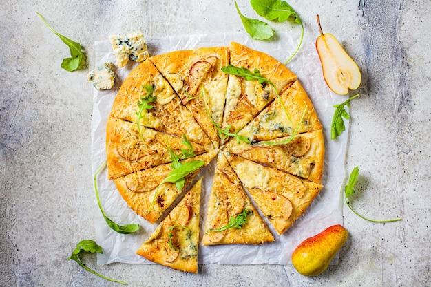 Pizza maison à la poire, roquette et fromage, fond gris