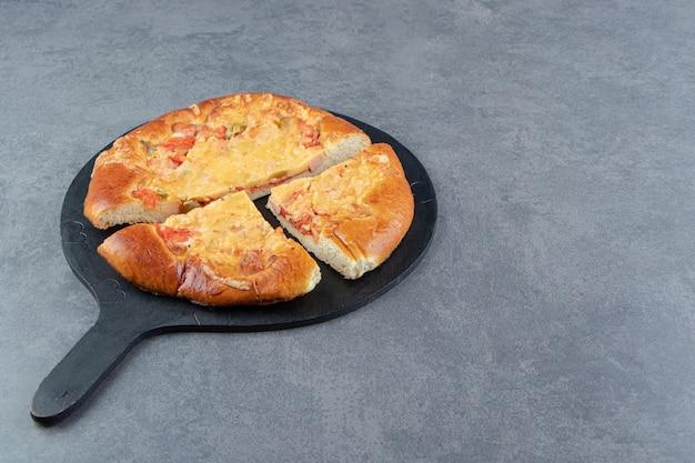Pizza maison en tranches sur une planche à découper noire.