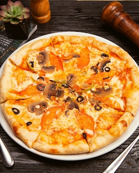 Pizza margarita aux olives noires, champignons, sauce tomate, tranches de tomate et fromage parmesan sur plaque blanche.