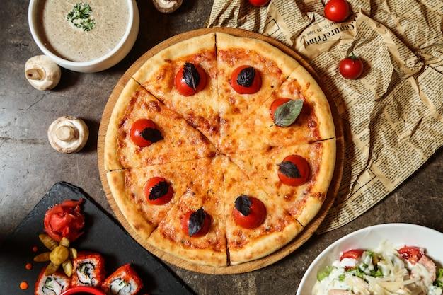 Pizza margarita sur la planche de bois fromage tomate basilic vue de dessus