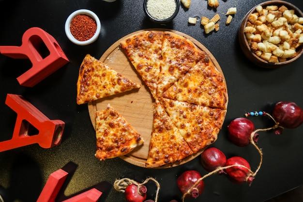 Pizza margarita sur la planche de bois pâte à fromage craquelins vue de dessus