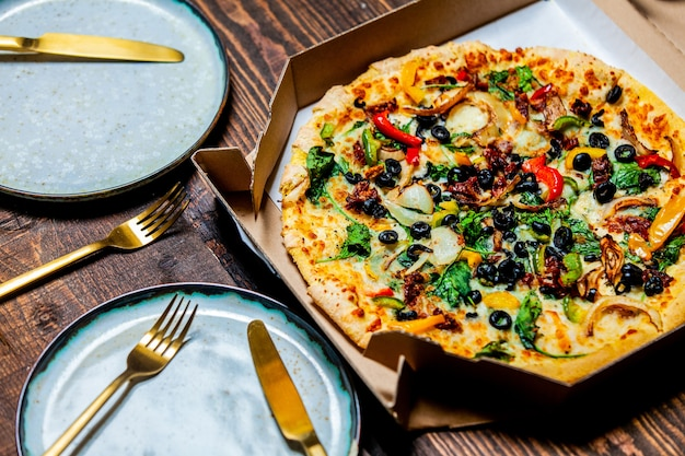 Pizza méditerranéenne aux olives et au fromage en carton et dans des assiettes sur une table
