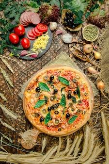 Pizza mélangée avec poulet, poivron, olives, oignons, basilic sur une planche à pizza