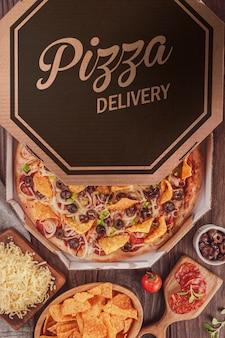 Pizza mexicaine avec mozzarella, oignon, pepperoni, olive noire, poivrons verts, nachos et origan dans une boîte de livraison (pizza mexicana) - vue de dessus.
