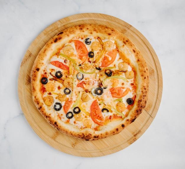 Pizza mixte avec olives, légumes et fromage fondu sur une planche de bois ronde.