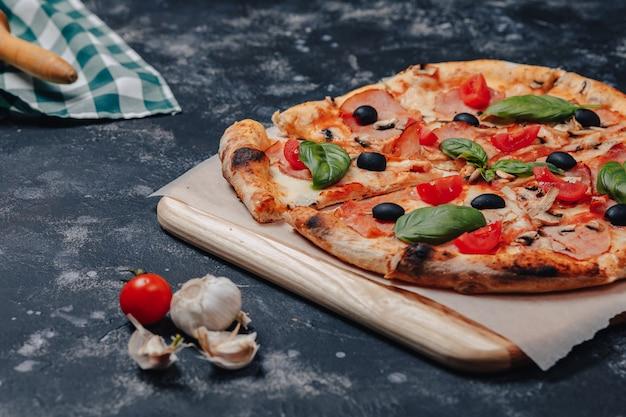 Pizza napolitaine appétissante sur un tableau noir avec divers ingrédients, espace libre pour le texte