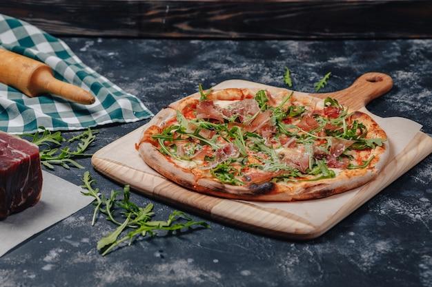 Pizza napolitaine appétissante sur un tableau noir avec divers ingrédients