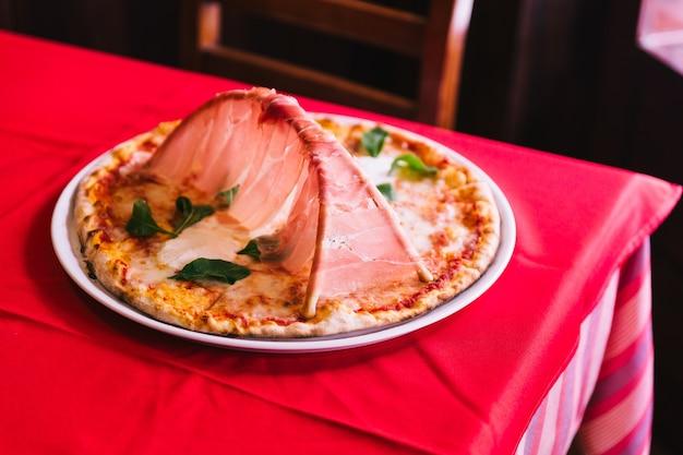 Pizza napolitaine à base de tomates et fromage mozzarella et garniture au jambon de parme