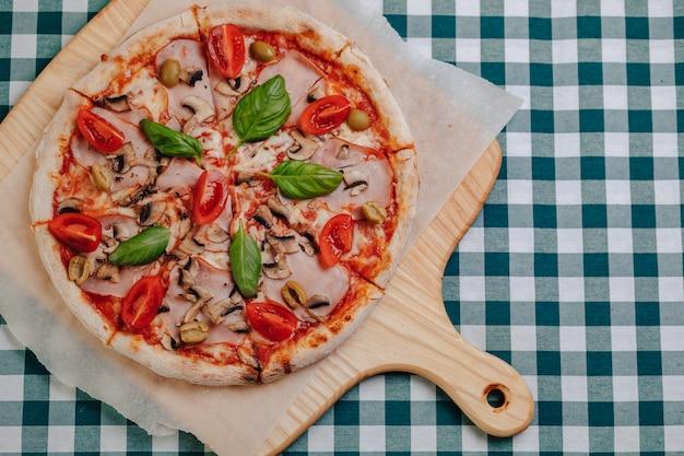 Pizza napolitaine avec jambon, fromage, roquette, basilic, tomates saupoudrées de fromage sur une planche de bois