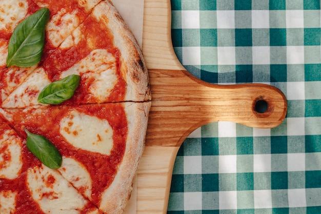 Pizza napolitaine avec jambon, fromage, roquette, basilic, tomates saupoudrées de fromage sur une planche de bois.