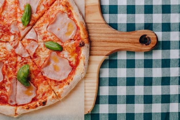 Pizza napolitaine avec jambon, fromage, roquette, basilic, tomates saupoudrées de fromage.