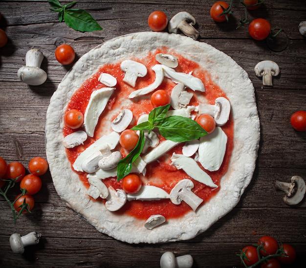 Pizza non cuite avec champignons frais, tomates cerises et mozzarella sur une table en bois rustique