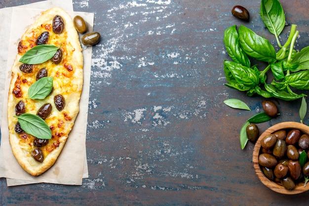 Pizza ovale faite maison avec des olives entières et du fromage