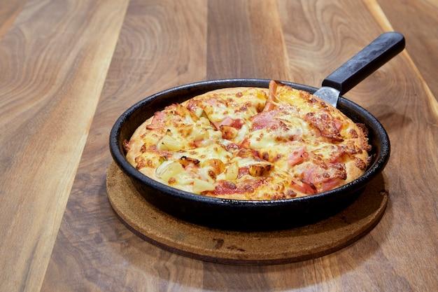 Pizza en planche à découper sur une vue de côté de table en bois.