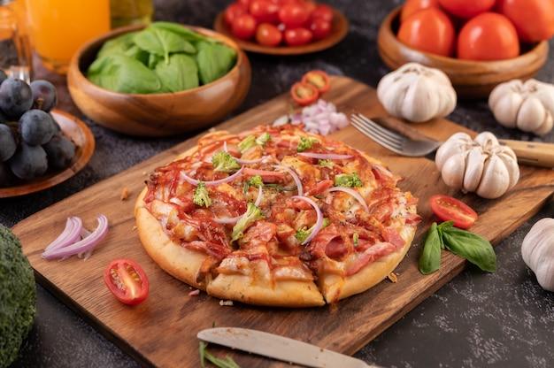 Pizza posée sur une assiette en bois.