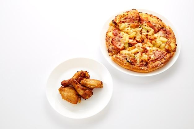 Pizza et poulets frits sont assiette blanche