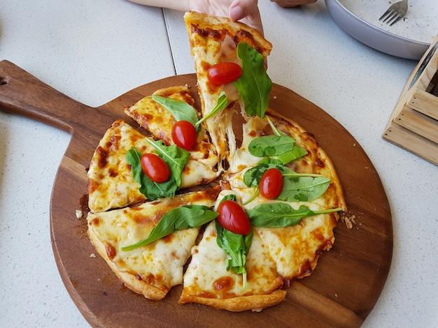 Pizza à quatre fromages avec salade de roquette et tomate cerise sur une plaque en bois