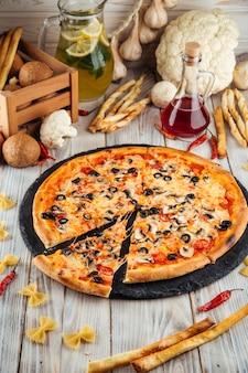 Pizza quatre saisons aux olives champignons et tomate