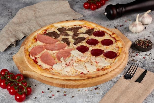 Pizza quatre saisons sur planche de bois, fond gris