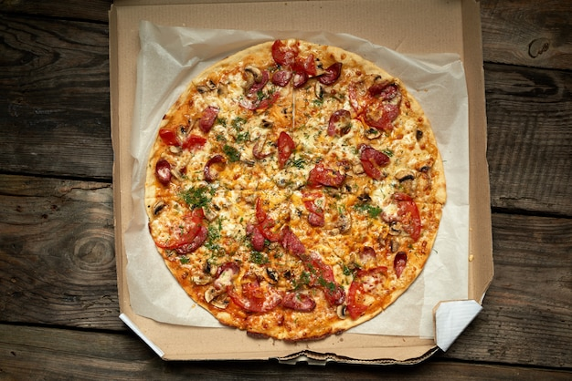 Pizza ronde cuite au four avec saucisses fumées, champignons, tomates, fromage et aneth dans une boîte en carton ouverte sur une table en bois