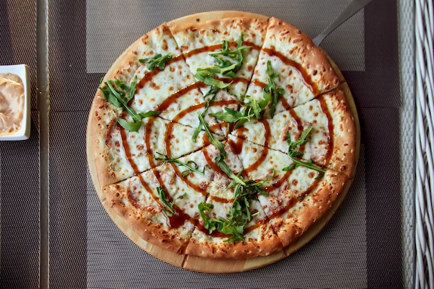 Pizza à la roquette sur une plaque en bois sur fond gris en terrasse d'été.