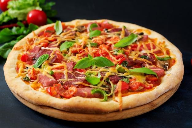 Pizza avec salami, jambon, tomate, fromage et champignons