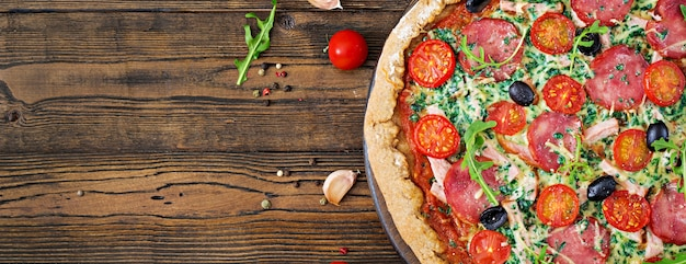 Pizza avec salami, tomates, olives et fromage sur une pâte avec de la farine de blé entier. vue de dessus